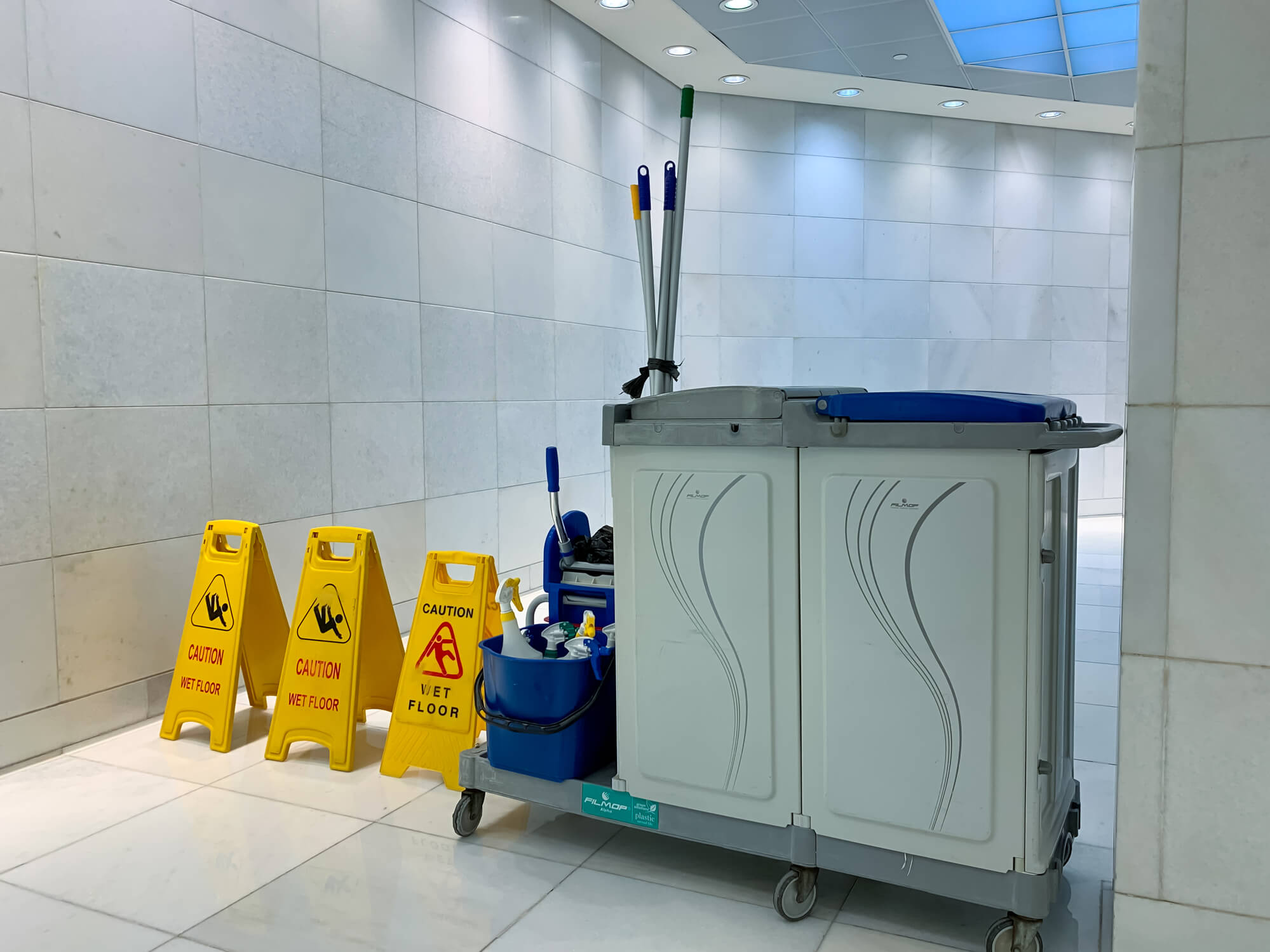 three yellow wet floor signs and a cleaning trolley with mop and bucket blocking access to a corridor in a commercial building