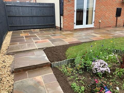 Paving and new fencing painted black in a domestic garden